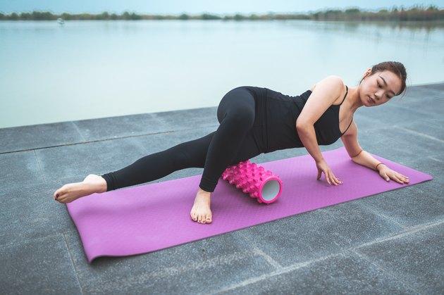 woman on an exercise mat using a foam roller
