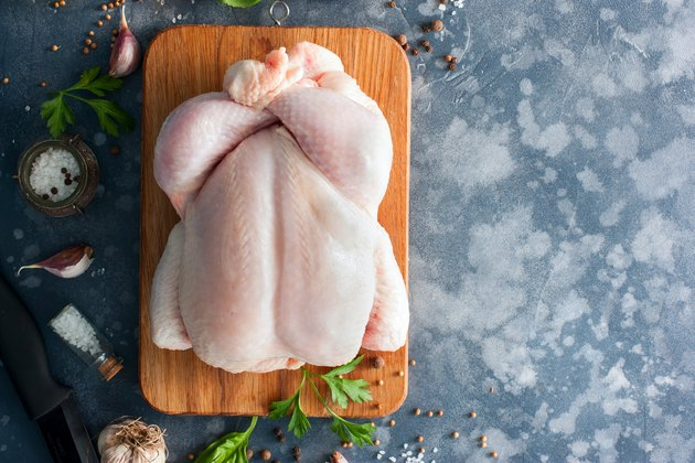 Whole raw chicken on a wooden board with spices for cooking, top view, horizontal, copy space
