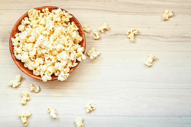 Salt popcorn in the wooden bowl on the wooden table.