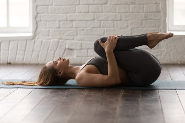 Young woman practicing yoga, lying in Knees to Chest pose, Apanasana