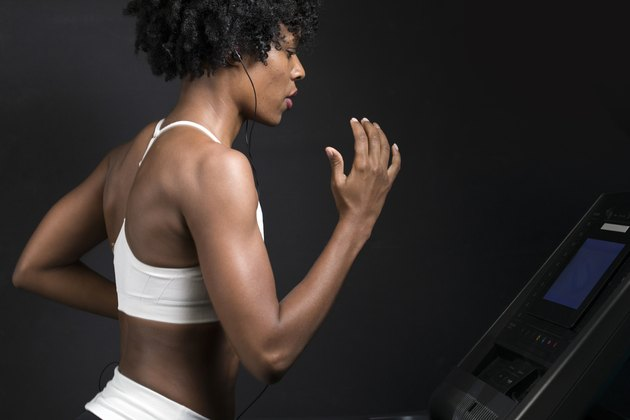 Side view of woman running on treadmill while listening music against wall in gym