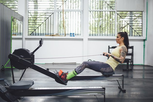 Athlete using rowing machine in gym