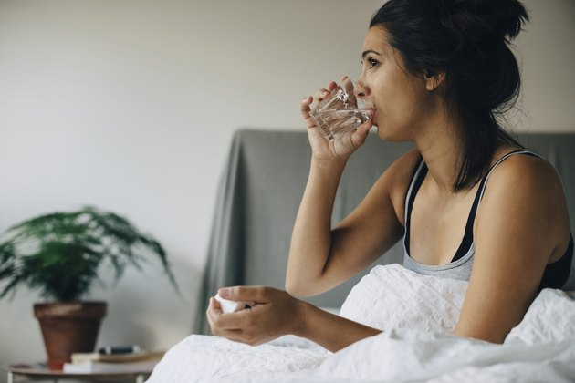 Woman taking medicine while sitting on bed at home