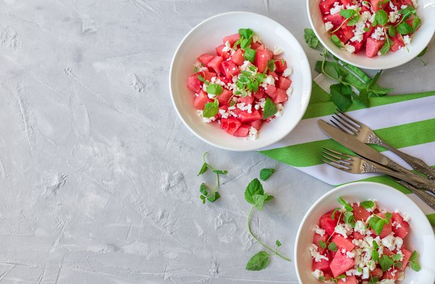 Fresh organic salad with watermelon, feta cheese and mint in bowls on light gray concrete background.