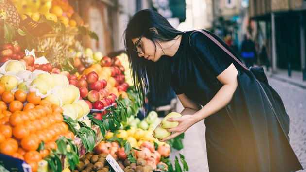Woman Buying Fruits on Street Market to eat a plant based diet on a budget