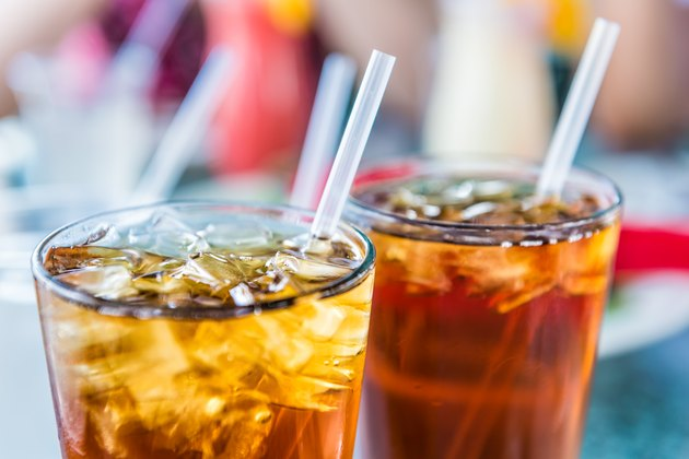 Macro closeup of iced tea or soda with ice cubes and straw in glass