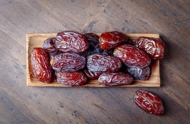 Juicy dates on wooden table .