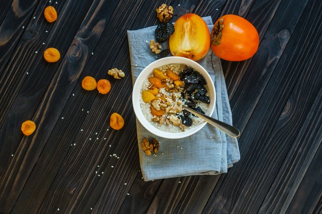 Oatmeal with Persimmon on a Black Wooden Table