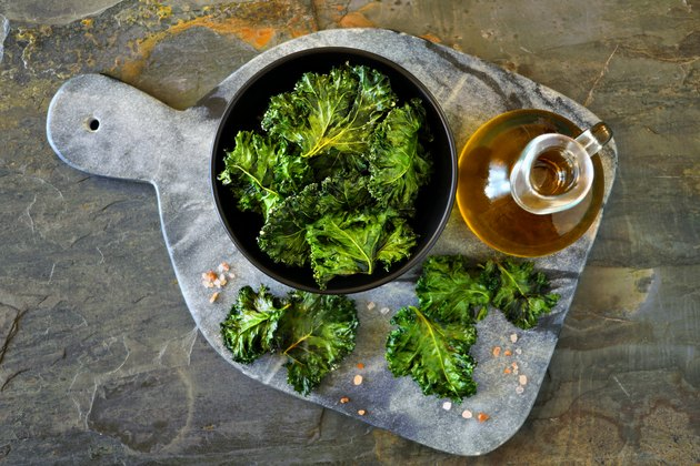 Platter of healthy kale chips, top view on slate