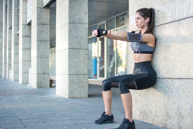Young sportswoman doing wall sit exercise outdoors.