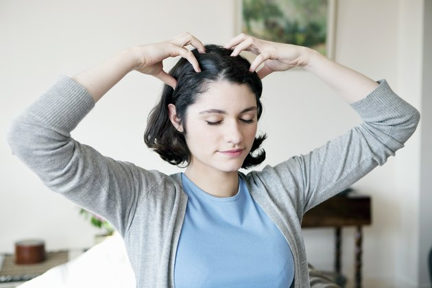 A woman with short brown hair performing a scalp exercise at home