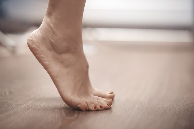 Feet of woman standing on tiptoe