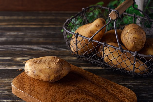 Raw unpeeled potatoes on wooden table