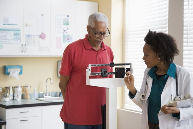 Female doctor weighing a senior man with diabetes