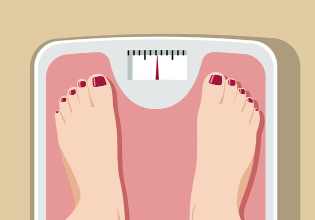 Feet on bathroom scale conveying obesity health risks