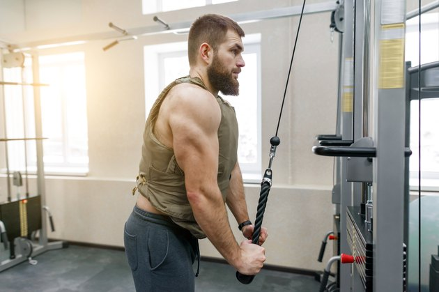 Muscular caucasian bearded man doing exercises dressed in weighted vest in the gym, military style