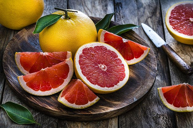 Whole and sliced grape fruit shot on rustic wooden table