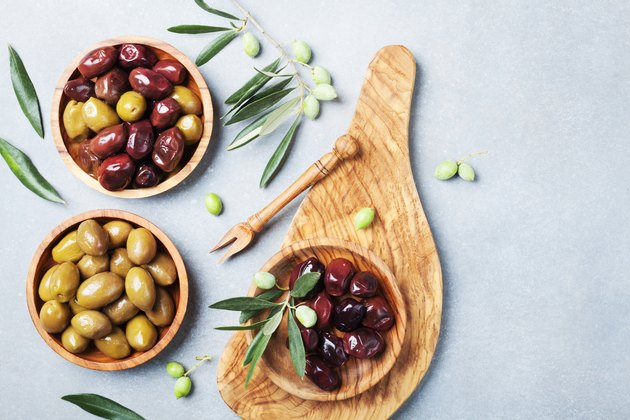 Natural greek olives in bowls with kitchen board from olive tree top view.