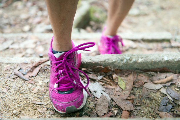 Hiker going up steps in pink sneakers and walking to lose weight