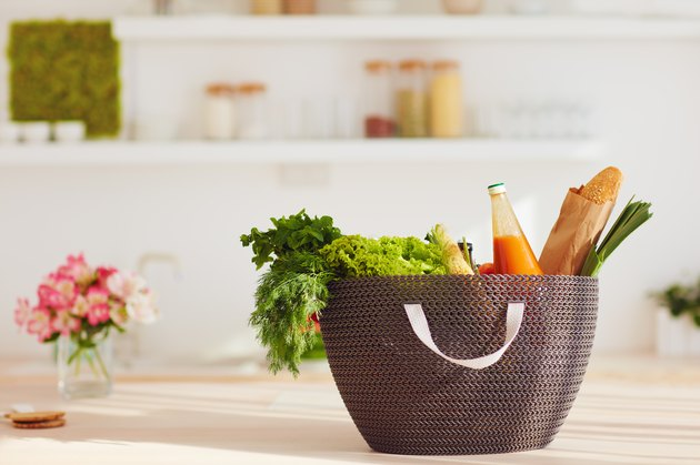 shopping bag full of fresh food on kitchen desk