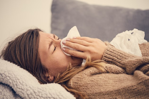 Sick woman with seasonal infections, flu, allergy lying in bed.