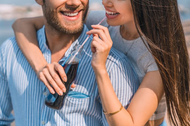 Close up shot of handsome young guy piggybacking his girlfriend drinking soft drink outdoors.