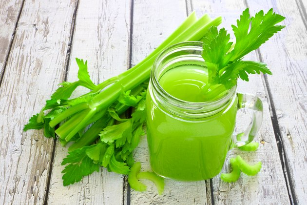 Celery juice in a mason jar against a white wood background