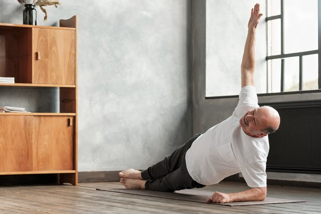 man doing a side plank exercise in living room to build muscle and lose stomach fat