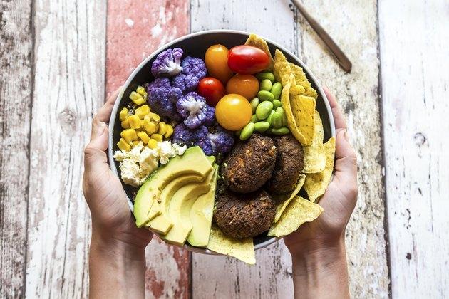 Holding choline-rich quinoa plant-based veggie bowl