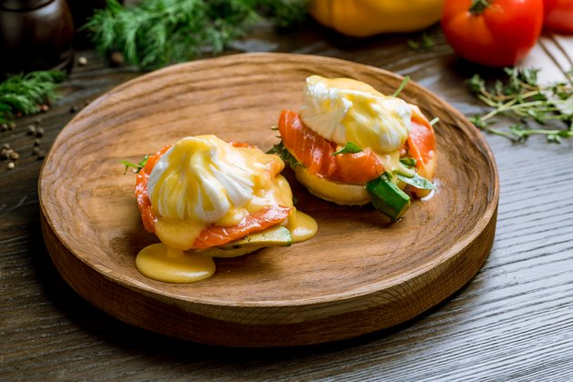 eggs Benedict with salmon and avocado on a wooden board