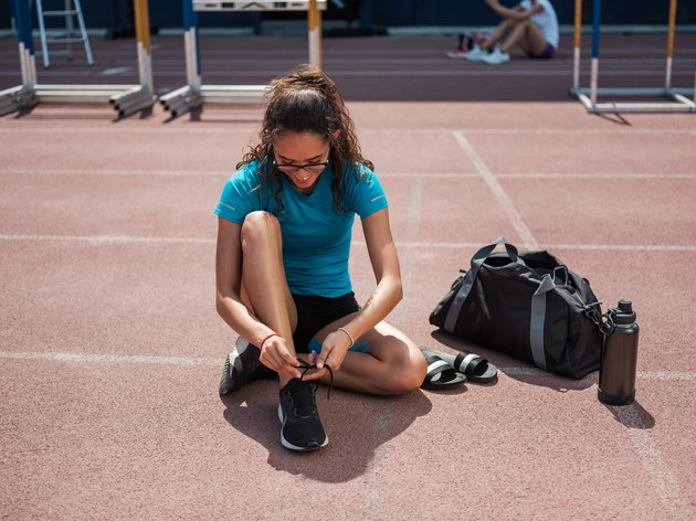 Latina athletic woman tying her shoes before running