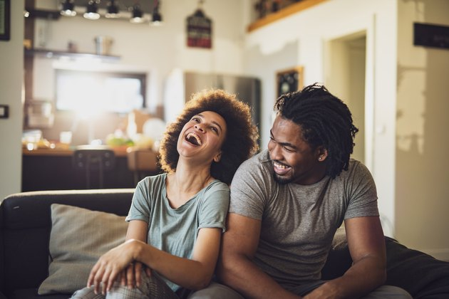 Young cheerful African American couple in the living room.