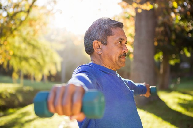 Man exercising with dumbbell on sunny day