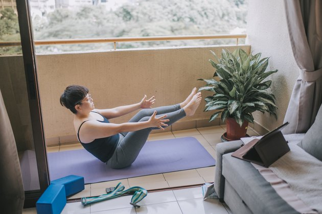 an asian mid adult woman workout yoga at home balcony during the restricted movement order in malaysia