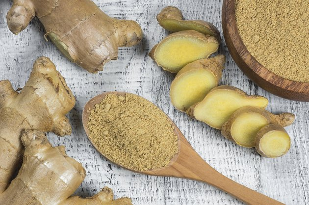 Fresh chopped ginger root and ground ginger powder in wooden spoon on wooden rustic table. Healthy food spice concept. Zingiber officinale