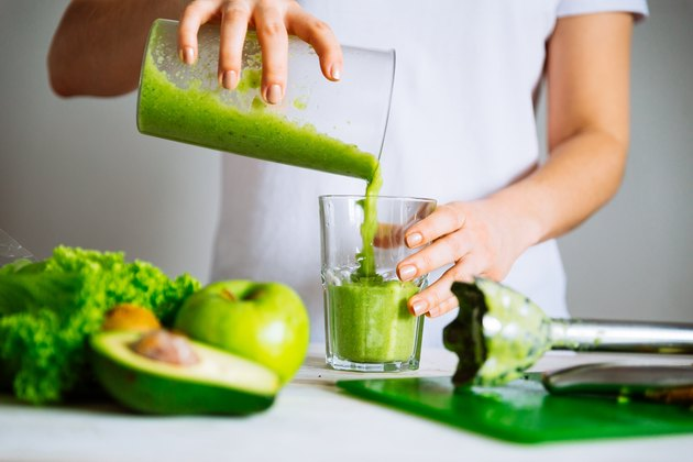 woman pouring green smoothie into glass