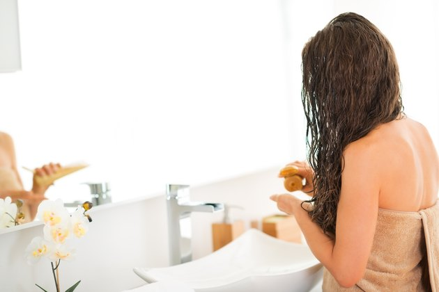 closeup on young woman applying hair mask in bathroom