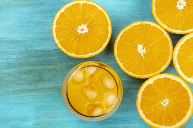 A photo of a glass of fresh orange juice with orange halves, shot from above on a vibrant blue background with a place for text