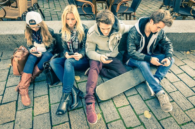 Group of young hipster friends playing with smartphone