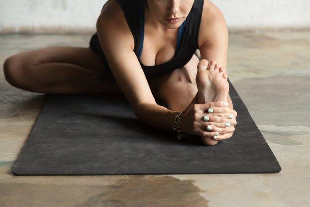 Young sporty woman in Janu Sirsasana pose, studio background