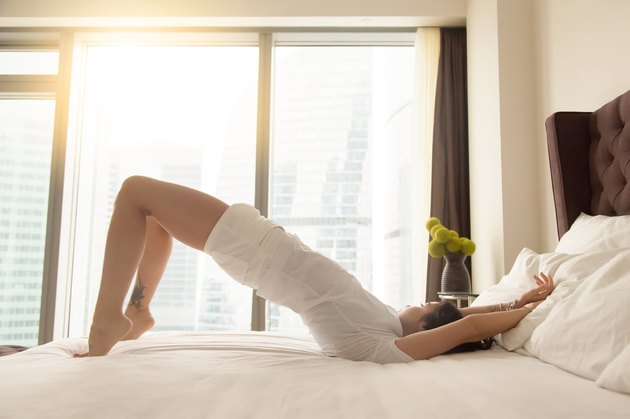 Young attractive woman in Glute Bridge pose on the bed