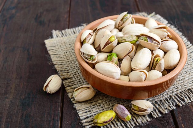 pistachios in a ceramic bowl on a dark wooden background.