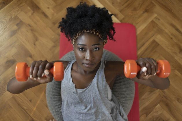 Woman doing a dumbbell chest press during an at-home workout