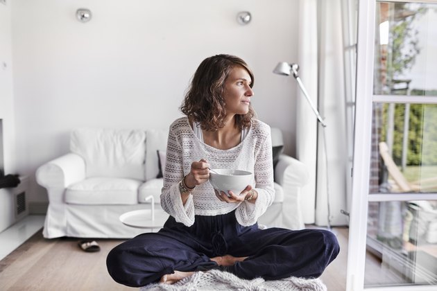 Young woman sitting in living room having breakfast