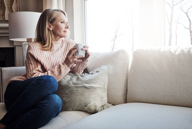 A woman drinking coffee on her couch while looking out the window