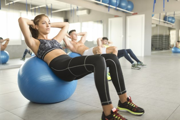 Woman doing ab exercises on a stability ball at the gym