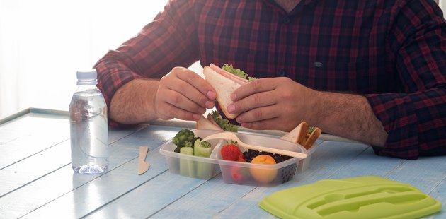 Man is eating healthy food of lunch box sitting at wooden table