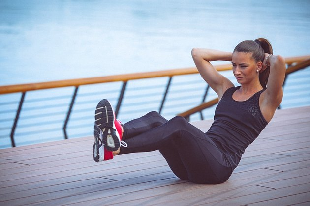 Young female athlete performs ab crunches outdoors
