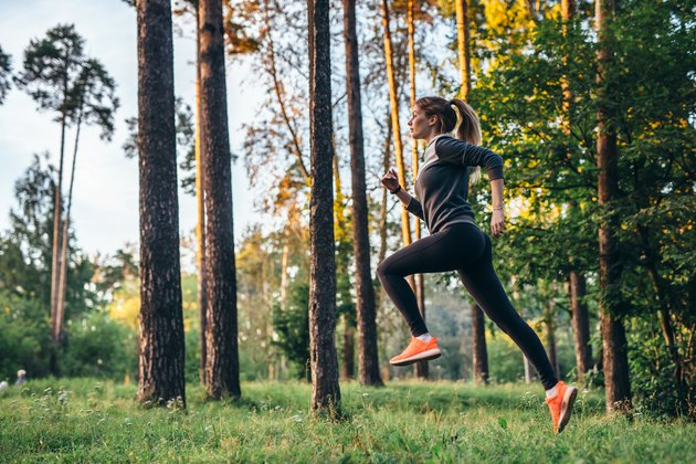 Young female athlete jogging in forest. Jogger doing morning physical training.