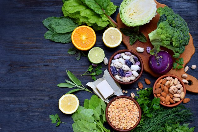 Composition on a dark background of products containing folic acid, vitamin B9 - green leafy vegetables, citrus, beans, peas, nuts, yeast. Top view. Flat lay